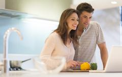 Smiling couple cutting bell peppers and looking at laptop in modern kitchen Stock Photos