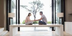 Stock Photo of Couple sitting on table face to face and holding hands, tree seen through patio
