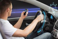 Man looking to smart phone while driving car Kuvituskuvat