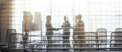 Business people standing in conference room shaking hands - stock photo