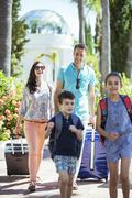 Family with luggage walking towards tourist resort - stock photo