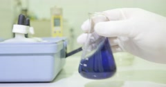A person mixing some chemicals in an Erlenmeyer flask Stock Footage