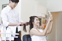 Female customer taking self portrait in barber shop - stock photo