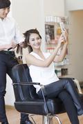 Stock Photo of Female customer taking self portrait in barber shop