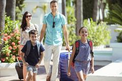 Family with suitcases walking towards tourist resort - stock photo