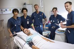 Team of doctors standing around smiling patient lying in bed in intensive care Kuvituskuvat
