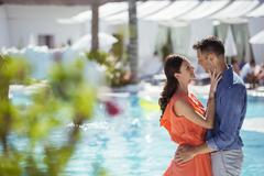 Couple standing face to face by swimming pool Stock Photos
