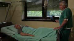 Injured patient lying in hospital bed and talking with doctor who holding x-ray. - stock footage