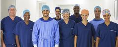 Group portrait of surgeons standing in hospital corridor - stock photo
