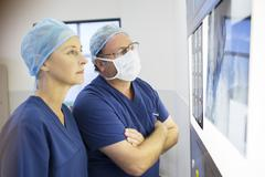 Stock Photo of Two  doctors discussing patient's x-ray and MRI before surgery