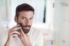 Man trimming beard in bathroom mirror Stock Photos