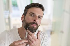 Man trimming beard in bathroom - stock photo