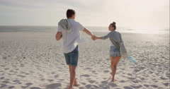 Young couple holding hands walking towards sunset on empty beach Stock Footage