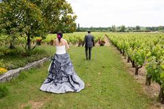 A newly wed couple walking through a vineyard - stock photo