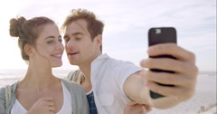 Happy couple taking selfies using mobile phone on beach at sunset Stock Footage