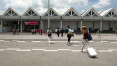 Couple walks from aircraft to airport, island vacation, sunny day, chase camera Stock Footage