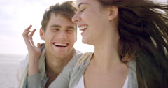 Happy couple taking selfie on beach at sunset using phone smiling and spinning - stock footage