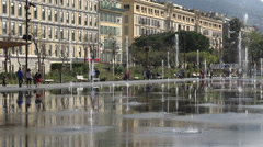 People walk past fountain water jets at Place Massena, Nice, France Stock Footage