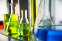 Close up of beakers with solutions on shelf in lab Stock Photos