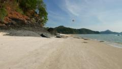 Move forward along beautiful beach, to rocky area and trees Stock Footage