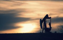 A pumpjack at an oil drilling site at sunset. - stock photo