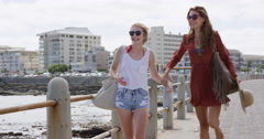 Two young women pointing at view on beach promenade enjoying carefree vacation Stock Footage