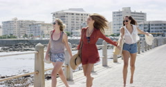 Three young women tourists on summer vacation walking on beach promenade - stock footage