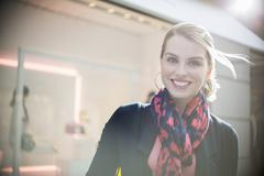 Woman standing in front of store in city - stock photo