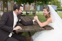 Young happy newly wed couple  fighting in arm wrestling - stock photo