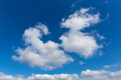 Fluffy white clouds in beautiful blue sky in spring - stock photo