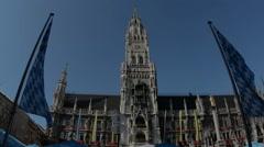 Clock tower in Marienplatz Munich framed by Bavarian flags Stock Footage