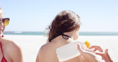 Teenage girlfriends helping each other putting on sunscreen on back for skin Stock Footage