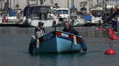 Two men in small fishing boat arrive at Nice port and marina, France Stock Footage