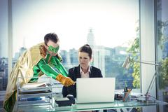 Superhero helping businesswoman working at office desk Stock Photos