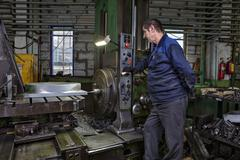 Work machine tool operator controls process of drilling steel part. Kuvituskuvat