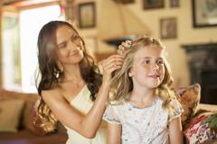 Bridesmaid helping girl with hairstyle in domestic room Stock Photos