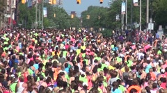 Women Runners head away from camera up road, thousands Stock Footage