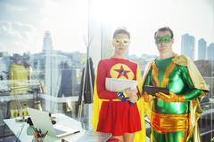 Superheroes standing in office - stock photo
