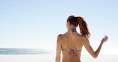 Beautiful young woman tying up hair on windy day on tropical beach slow motion Stock Footage