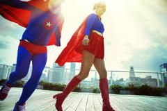 Superheroes running on city rooftop - stock photo