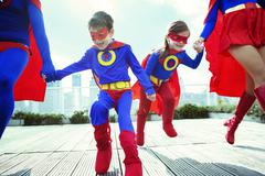 Family of superheroes running on city rooftop - stock photo