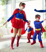 Family of superheroes playing in living room - stock photo