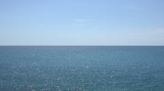 Clear blue sea water sparkles in the sun with sky and horizon Stock Footage