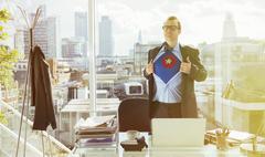 Businessman revealing superhero costume under suit Stock Photos