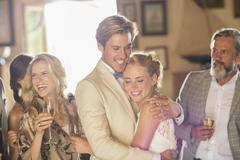 Young couple and guests at wedding reception in domestic room - stock photo
