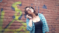 Girl listening to music on the background wall Stock Footage