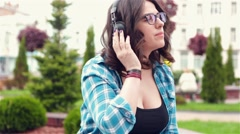 Girl listening to music in the park Stock Footage