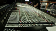 Man working on professional digital audio channel mixer in studio - stock footage