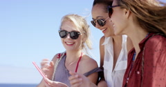 Teenage girls using mobile phone sharing photo of summer vacation on social Stock Footage