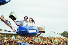 Couple enjoying ride on carousel in amusement park Kuvituskuvat